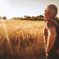 Photo of a senior man, hiking in the nature and exploring, at sunset